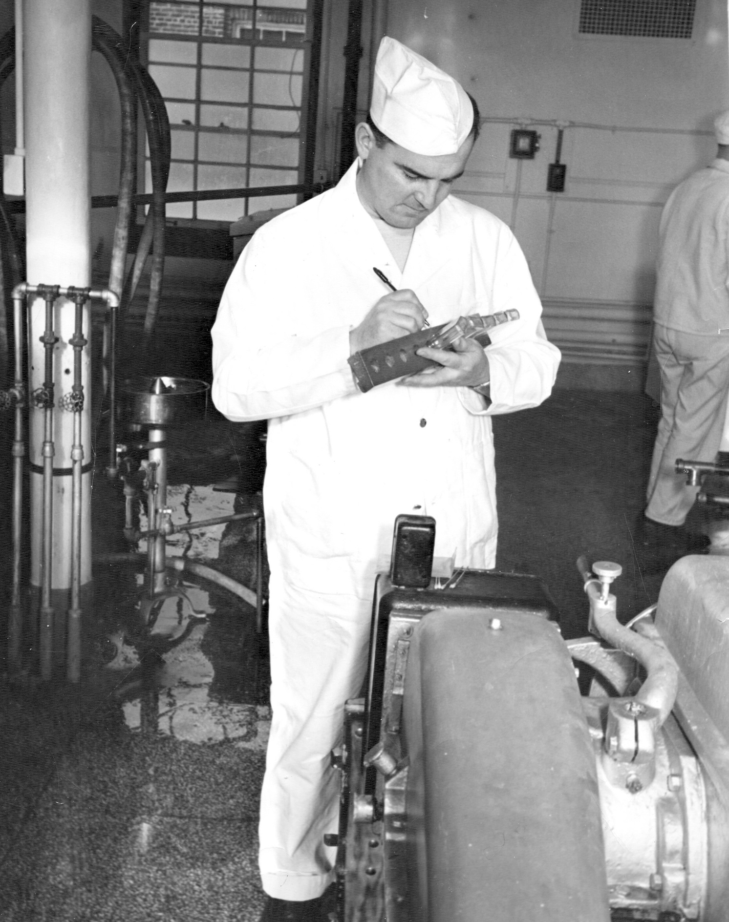 Prise d'échantillons de lait pour une analyse dans le laboratoire de la laiterie. <b>Roger Landreville, employé de l'usine de J.J. Joubert, vers 1949.</b> Collection Julie Landreville