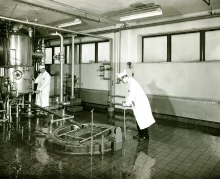 Deux employés s'affairent près d'un cuiseur pour la confiture, vers 1955. Archives – HEC Montréal, Fonds Alphonse Raymond, P078/Z, 0001