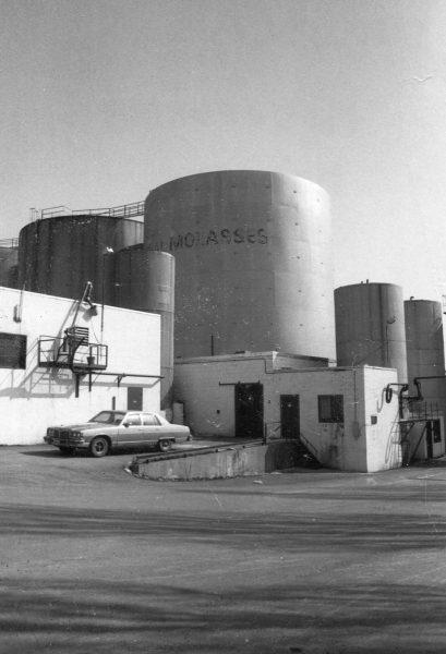 Imperial Molasses molasses tanks on Notre-Dame Street at the corner of Iberville Street, circa 1970. Écomusée du fier monde.