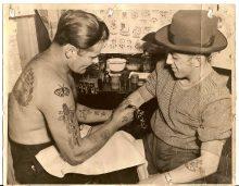 Clément Demers tatoue un client dans son premier studio de tatouage, rue York, Ottawa, 26 février 1949. Fonds Clément Demers. Écomusée du fier monde.